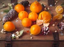 Os mandarino encontram-se em uma caixa de madeira velha, cones do pinho fotografia de stock royalty free