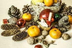 Os mandarino, porcas, flocos de neve, bolas, cestas da palha com frutos Fotografia de Stock Royalty Free