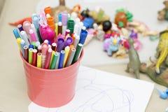 Os marcadores coloridos estão na cubeta cor-de-rosa Imagem de Stock