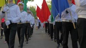Os marinheiros novos no uniforme com as varas nas mãos jogam em cilindros grandes durante o março e levam bandeiras coloridas na  vídeos de arquivo