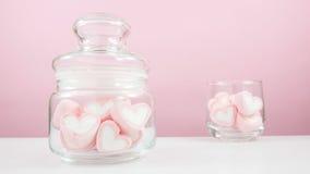 Os marshmallows cor-de-rosa bonitos do coração no frasco de vidro pequeno Fotografia de Stock
