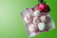 Os marshmallows cor-de-rosa e brancos em uma placa branca com as borboletas, isoladas aumentaram em um fundo verde Imagens de Stock