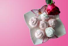 Os marshmallows cor-de-rosa e brancos em uma placa branca com as borboletas, isoladas aumentaram no fundo cor-de-rosa Imagem de Stock