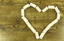 Os marshmallows do rosa da forma do coração no fundo fotos de stock