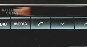 Os meios e a navegação controlam botões de um carro moderno imagens de stock