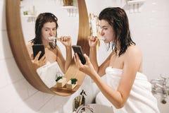 Os meios sociais afetam Mulher feliz nova nos dentes de escovadela de toalha branca e vista da tela do telefone no banheiro à mod imagens de stock royalty free