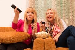Os melhores amigos em casa que olham a tevê e que bebem o estilo retro do vinho filtraram a imagem Imagens de Stock