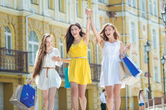 Os melhores amigos fazem uma compra! Meninas que guardam sacos de compras e wa Imagem de Stock