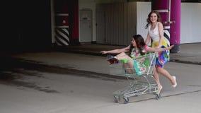 Os melhores amigos passam o tempo junto e têm o divertimento o amigo conduz a amiga em um trole no parque de estacionamento Movim video estoque