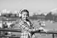 Os melhores apps da música que merecem a escutar A criança da menina escuta música fora com fones de ouvido modernos Escute livre foto de stock royalty free
