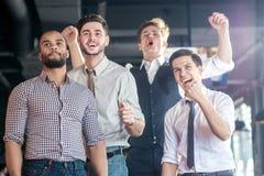 Os melhores fãs que olham a tevê e o futebol do prazer Quatro homens bem sucedidos Imagens de Stock Royalty Free