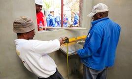 Os membros da Comunidade diversos juntam-se ao pessoal de PWC em construir uma baixa casa custada em Soweto fotos de stock