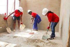 Os membros da Comunidade diversos juntam-se ao pessoal de PWC em construir uma baixa casa custada em Soweto fotos de stock royalty free
