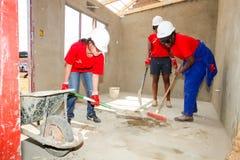Os membros da Comunidade diversos juntam-se ao pessoal de PWC em construir uma baixa casa custada em Soweto fotografia de stock