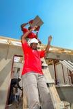 Os membros da Comunidade diversos juntam-se ao pessoal de PWC em construir uma baixa casa custada em Soweto imagem de stock