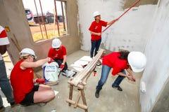 Os membros da Comunidade diversos juntam-se ao pessoal de PWC em construir uma baixa casa custada em Soweto imagem de stock royalty free