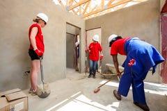 Os membros da Comunidade diversos juntam-se ao pessoal de PWC em construir uma baixa casa custada em Soweto foto de stock royalty free