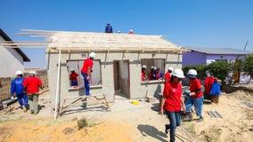 Os membros da Comunidade diversos juntam-se ao pessoal de PWC em construir uma baixa casa custada em Soweto imagens de stock