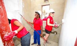 Os membros da Comunidade diversos juntam-se ao pessoal de PWC em construir uma baixa casa custada em Soweto foto de stock