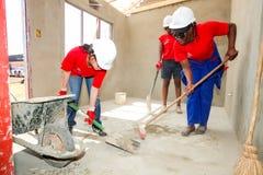 Os membros da Comunidade diversos juntam-se ao pessoal do ` s de PWC em construir um baixo cos imagens de stock