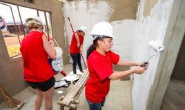 Os membros da Comunidade diversos juntam-se ao pessoal do ` s de PWC em construir um baixo cos imagem de stock