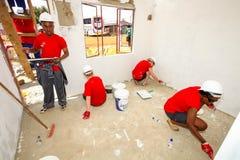 Os membros da Comunidade diversos juntam-se ao pessoal do ` s de PWC em construir um baixo cos fotos de stock