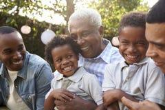 Os membros da família masculinos da multi geração recolheram em um jardim imagens de stock
