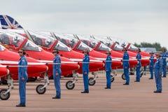 Os membros do grupo à terra de Royal Air Force RAF Red Arrows dão sentidos aos pilotos em seu falcão T do espaço aéreo britânico  imagem de stock