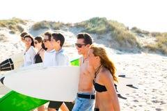 Os meninos adolescentes e as meninas do surfista agrupam o passeio na praia Imagem de Stock