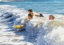 Os meninos adolescentes têm a natação do divertimento nas ondas Fotos de Stock Royalty Free