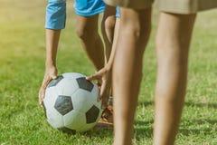 Os meninos asi?ticos praticam retroceder a bola para marcar objetivos imagens de stock