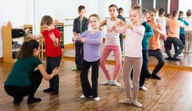 Os meninos atentos e as meninas que ensaiam o bailado dançam no estúdio Fotografia de Stock