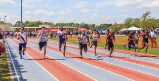 Os meninos competem em um calor de 200 medidores em com convite imagens de stock