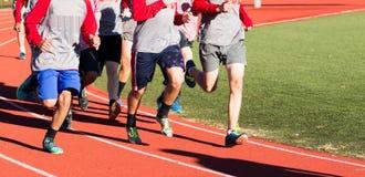 Os meninos de corta-mato team running rapidamente em uma trilha nos pontos Foto de Stock Royalty Free