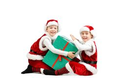 Os meninos de riso felizes adoráveis em Santa vestem guardar a caixa de presente do Natal Fundo branco isolado fotografia de stock royalty free