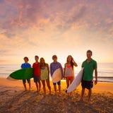 Os meninos e as meninas dos surfistas agrupam o passeio na praia Fotografia de Stock Royalty Free