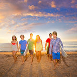 Os meninos e as meninas dos surfistas agrupam o passeio na praia Foto de Stock Royalty Free