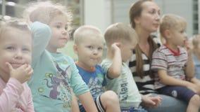 Os meninos e as meninas felizes sentam-se no banco com Berçário-educadora vídeos de arquivo