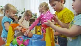Os meninos e as meninas pequenos alegres jogam com brinquedos e estudo video estoque