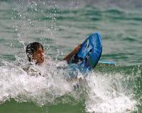 Os meninos esforçam-se montando as ondas Fotografia de Stock Royalty Free