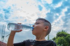 Os meninos estão bebendo a água fria imagem de stock royalty free
