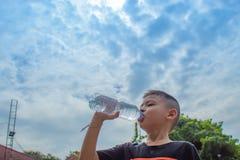 Os meninos estão bebendo a água fria imagens de stock royalty free