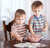 Os meninos estão misturando o mincemeat em uma bacia imagens de stock