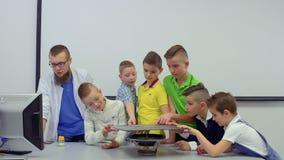 Os meninos examinam a placa do chladni e vibrações sadias