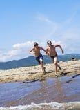 Os meninos funcionam na água Foto de Stock