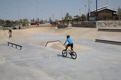Os meninos montam a bicicleta no parque Frisco Texas do patim fotografia de stock