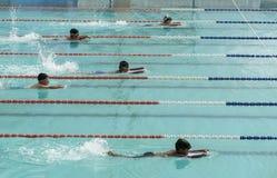Os meninos nos óculos de proteção e na natação do tampão competem a ação Fotos de Stock Royalty Free