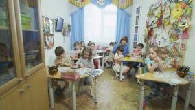 Os meninos que as meninas se sentam em tabelas fazem aplicações no pré-escolar filme