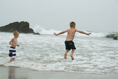 Os meninos que saltam na água na praia Imagens de Stock