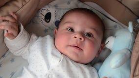 Os 3 meses bonitos do bebê idoso que faz as caras engraçadas no bebê levam o berço video estoque